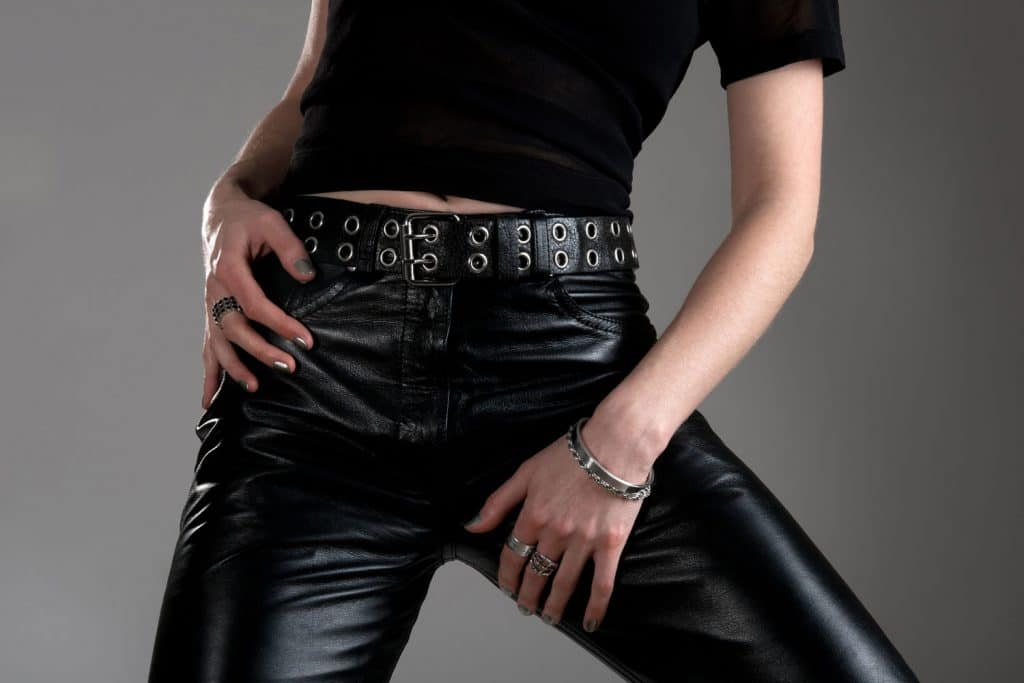 An unrecognizable woman wearing a black shirt and leather pants
