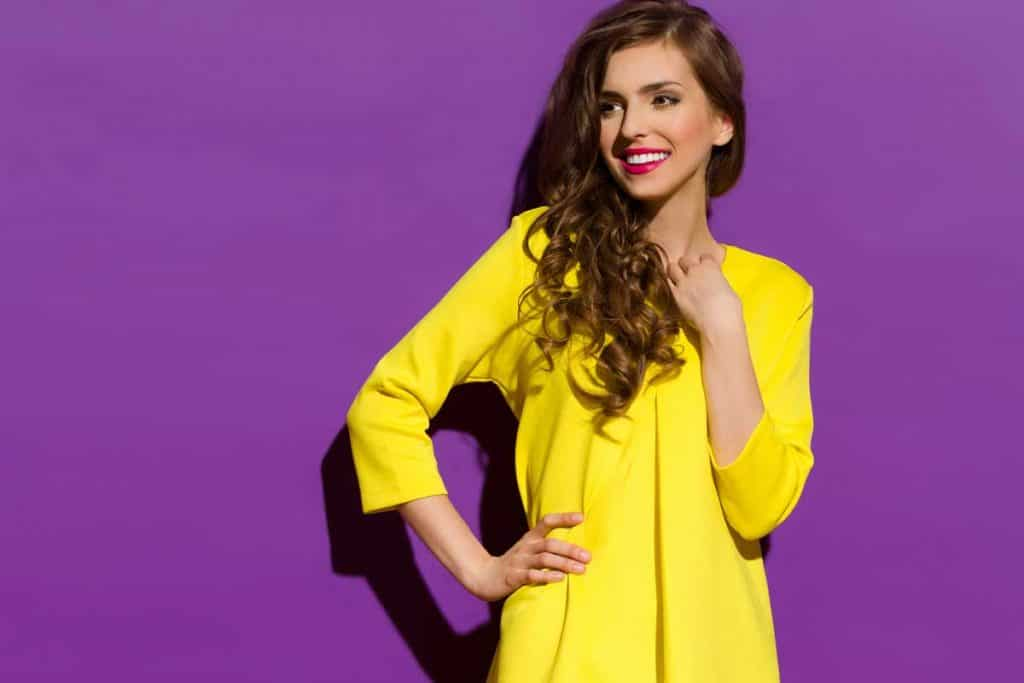 Beautiful smiling girl in yellow mini dress posing with hand on hip, What Color Lipstick Goes With A Yellow Dress?