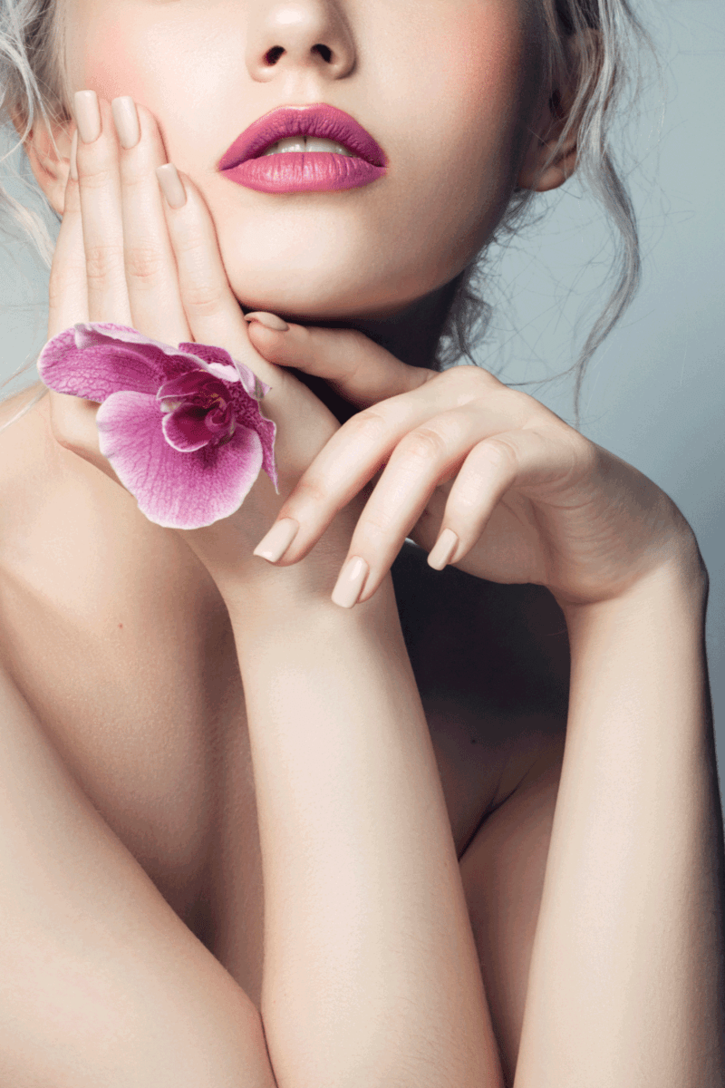 Beautiful woman holding a flower and wearing dusty pink lipstick