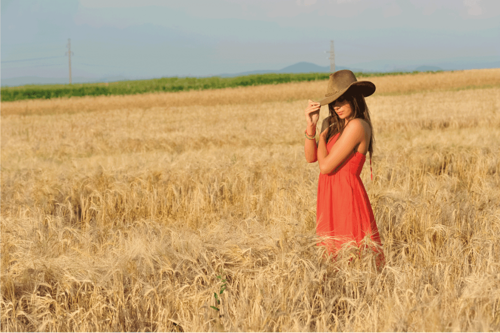 Beautiful woman with orange dress and hat standing in wheat field. What Color Lipstick Goes With An Orange Dress