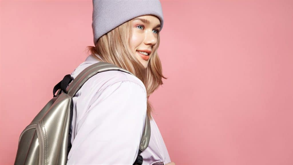 Cheerful girl with nice appearance in casual jacket and cap with trendy backpack. Isolated on pink background