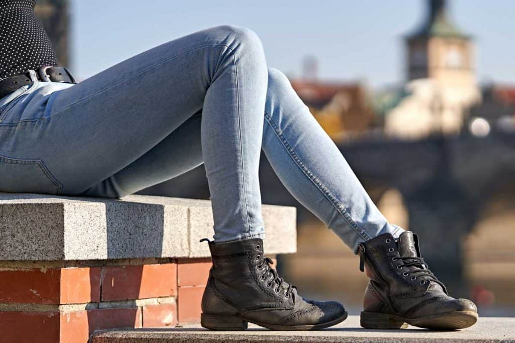 Close-up of a female sitting down on a stone wall and dressing casual skinny jeans, Do Skinny Jeans Get Loose? [With Ways To Prevent Stretching]