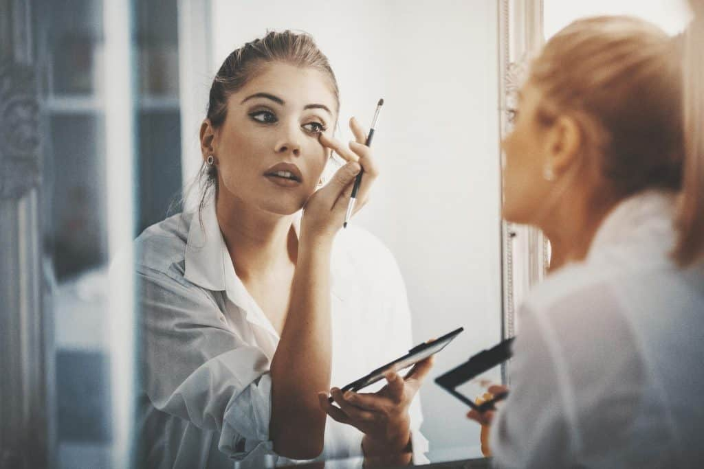 Closeup of attractive mid 20's blond woman putting on some makeup in front of large bathroom mirror