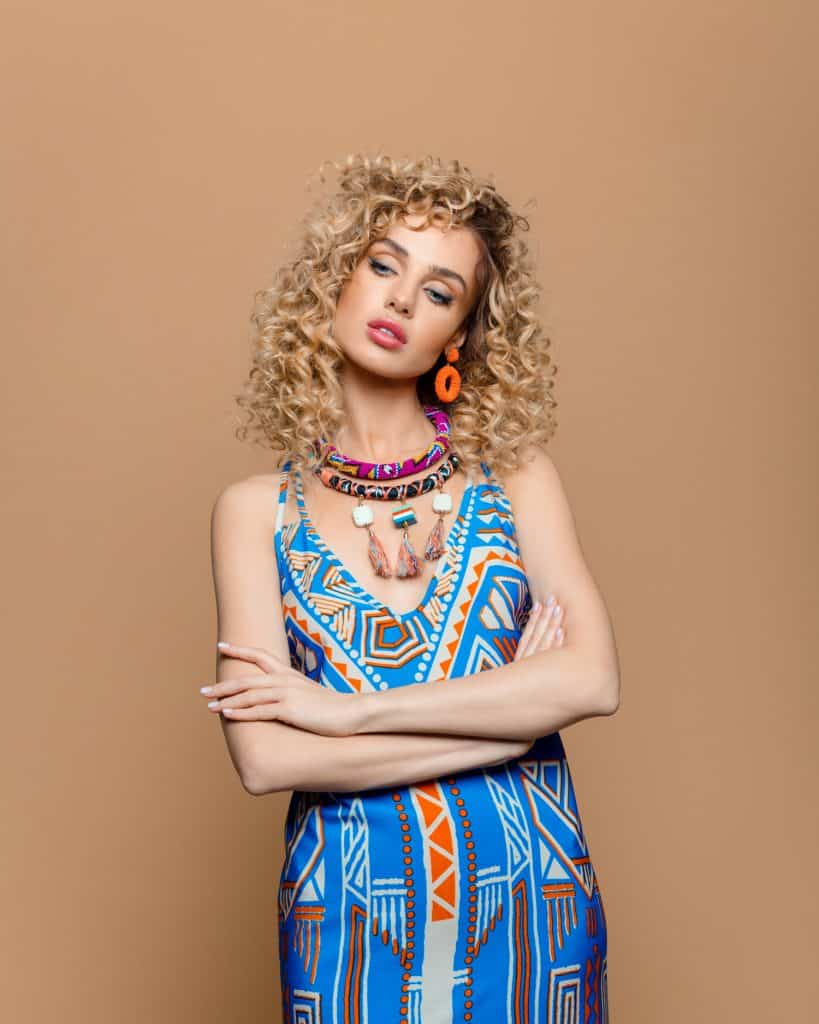 Curly hair woman in boho style outfit against brown background