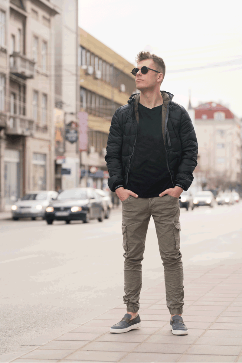 Fashion portrait of a young man standing on the street wearing jacket and cargo pants