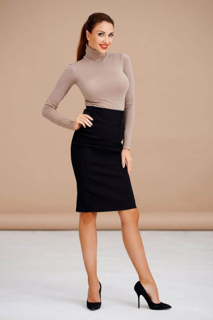 Fashionable brunette wearing turtle neck and black pencil skirt