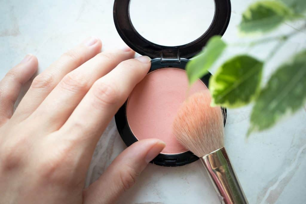 Female hand holding opened blush powder and brush in interior. Top view, Close-up, make-up concept