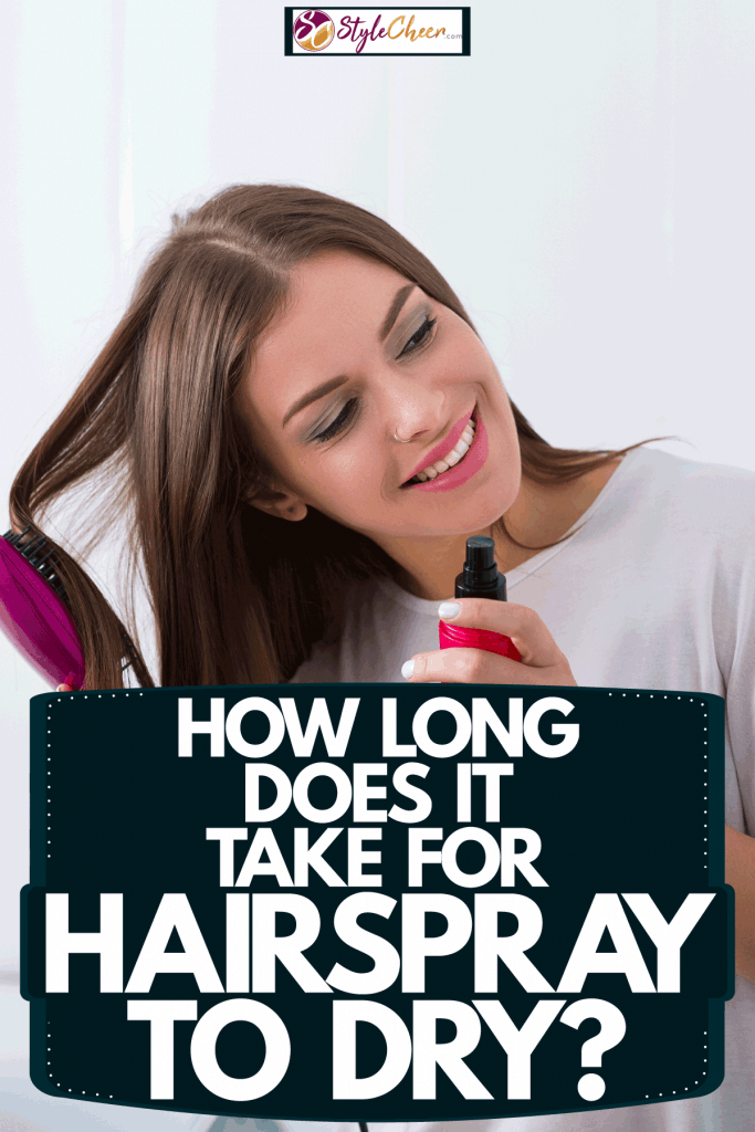 A woman combing her hair and holding a hairspray inside her powder room, How Long Does It Take For Hairspray To Dry?