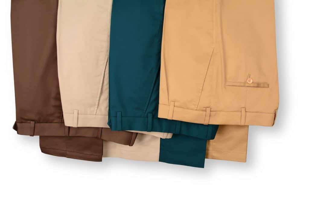 Khaki and dark blue colored trousers hanged on a white background