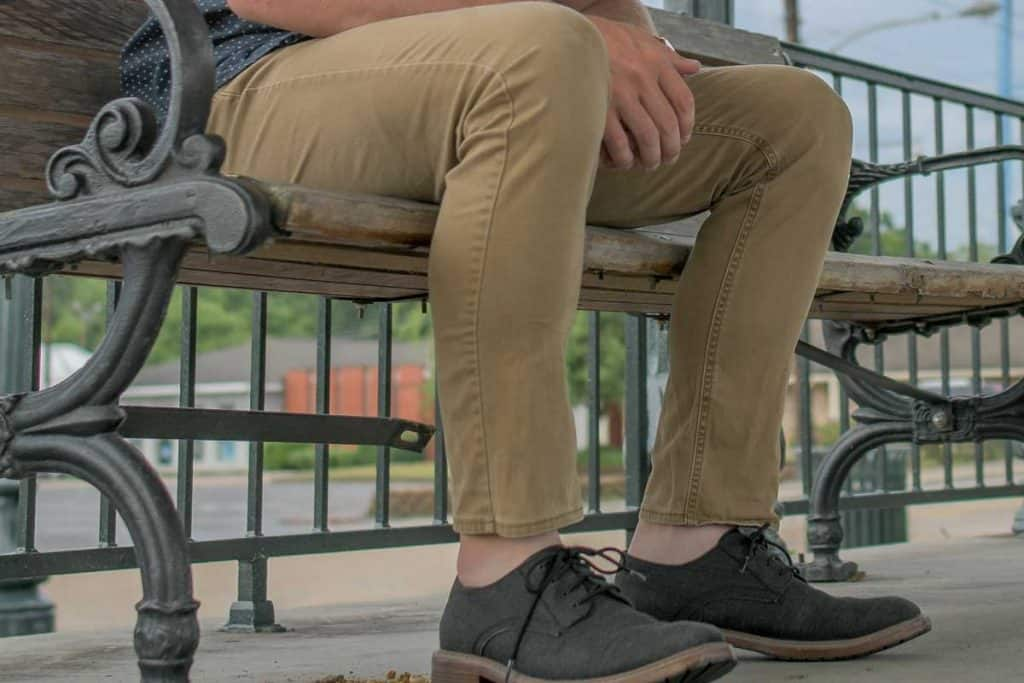 Man sitting on the bench wearing khaki pants and black leather shoes, What Color Shoes Go With Khaki Pants?