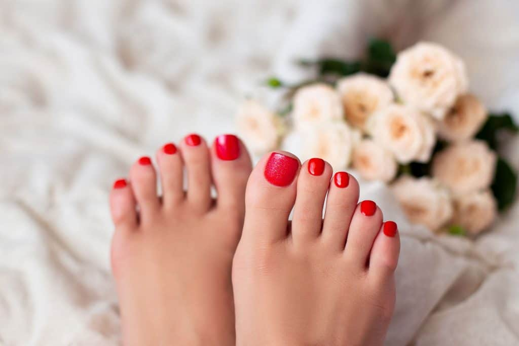 Perfectly done pedicure with red glitter nail polish, How Long Does A Pedicure Take? [By Type Of Pedicure]