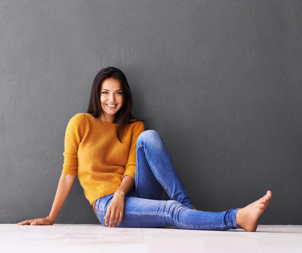 Young woman sitting on the floor wearing skinny jeans
