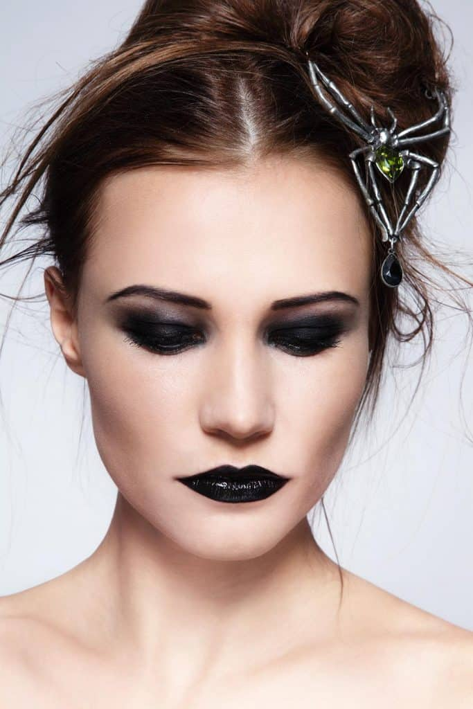Portrait of young beautiful woman with messy hairdo and black lipstick