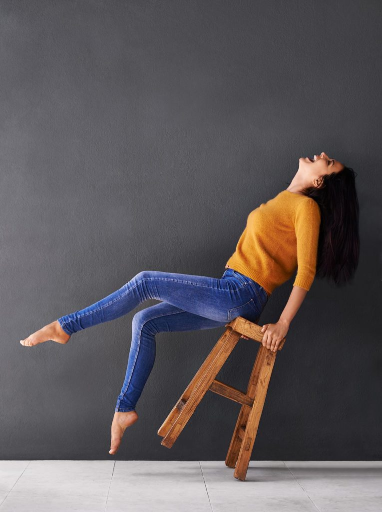 Shot of a happy young woman laughing while leaning back on a stool