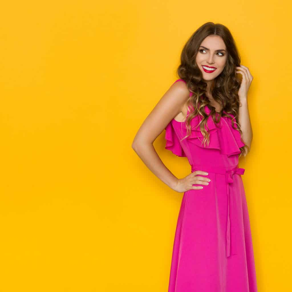 Smiling young woman in elegant pink dress is holding hand on hip and looking away over the shoulder. Three quarter length studio shot against yellow background.