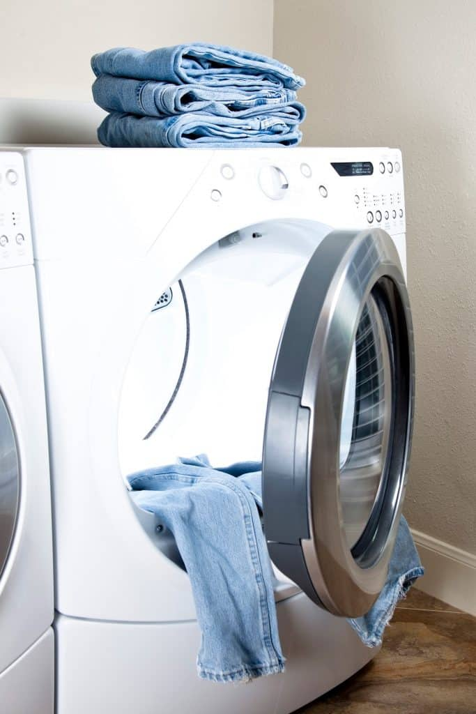 Stack denim jeans. Energy efficient, front load dryer. Drying laundry.