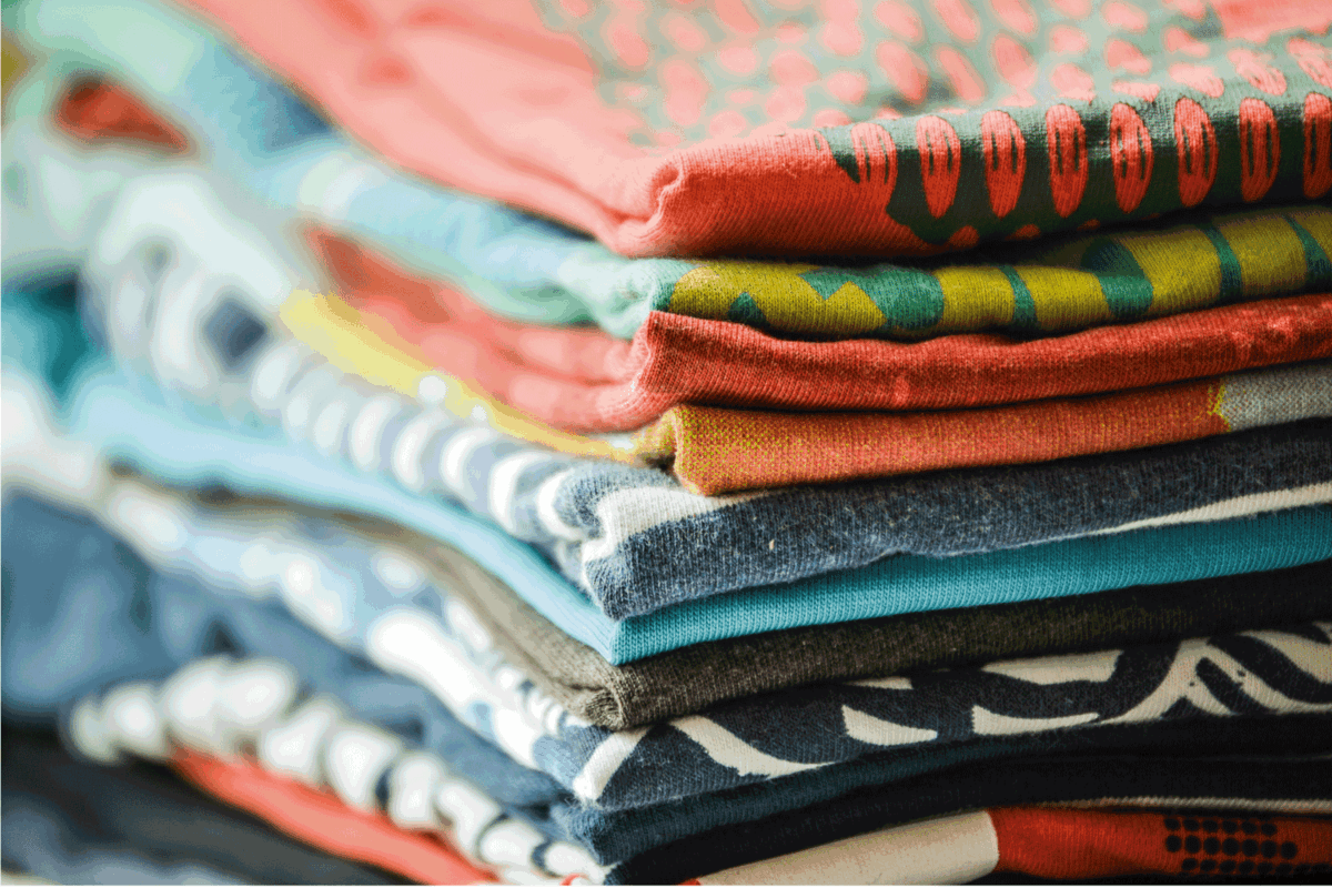 T-shirts in several colours folded and piled on top of each other