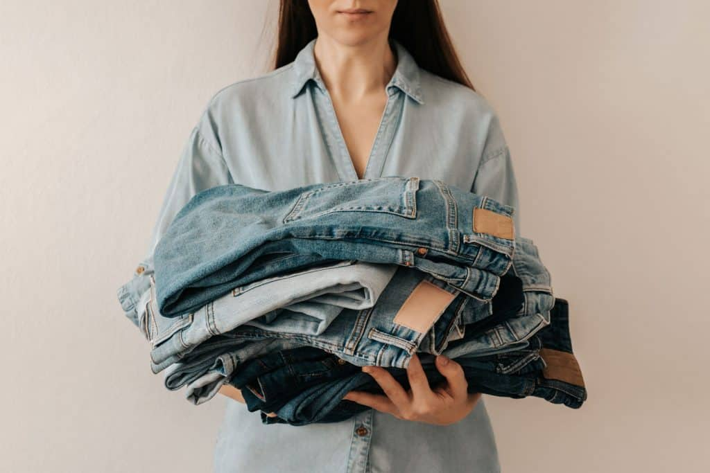 Unrecognizable woman holds stack of lot jeans pants on white background, How Often Should You Wash Pants? [A Breakdown By Type]