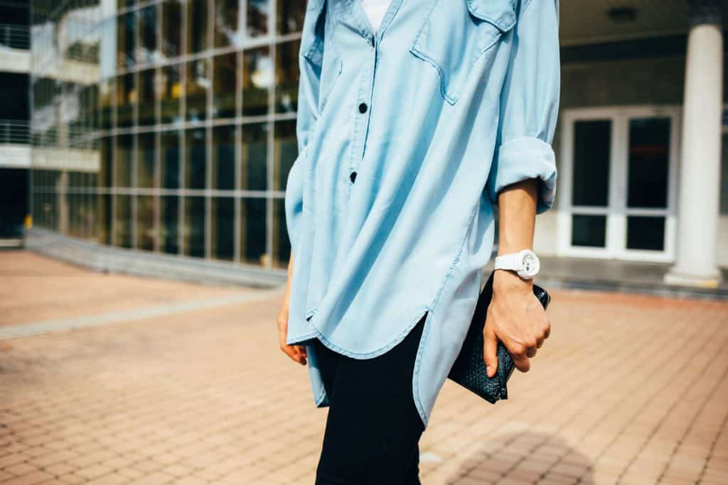 Unrecognizable young woman wearing oversize denim tunic shirt, black jeans and white wristwatches holding clutch bag standing outdoors in city on summer day, Can You Wear Tunics With Jeans? [With 6 Stylish Outfit Suggestions!]