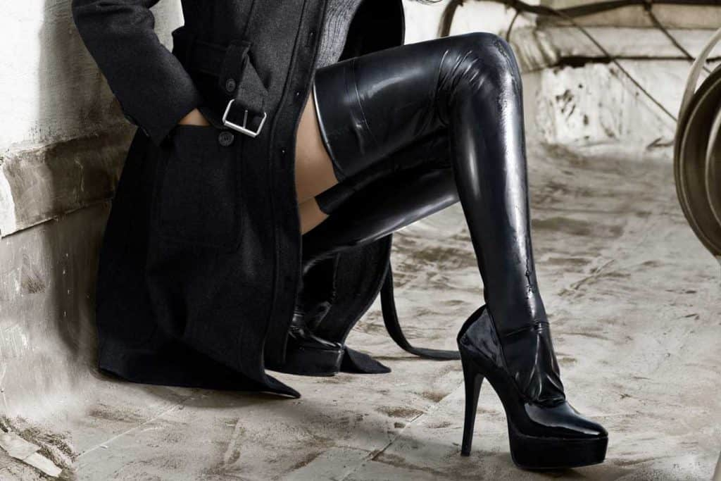 Woman wearing black thigh-high boots on a rooftop, What Socks To Wear With Thigh-High Boots