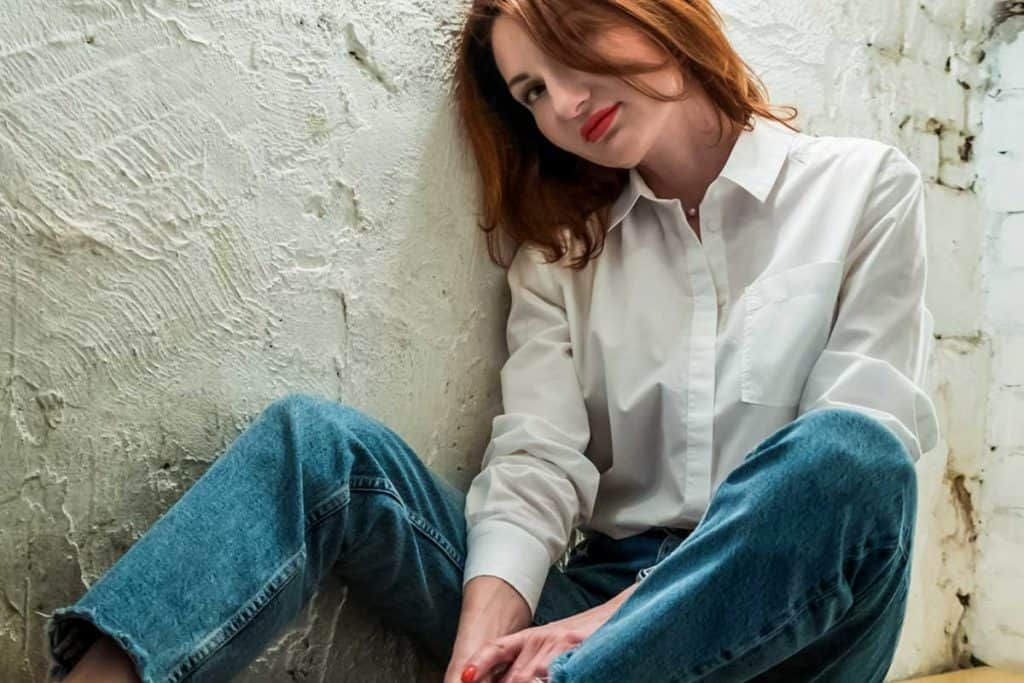 Woman with red lips in jeans and white shirt sits on wooden bench, What Color Lipstick Goes With Jeans? [A Look At Top Choices]