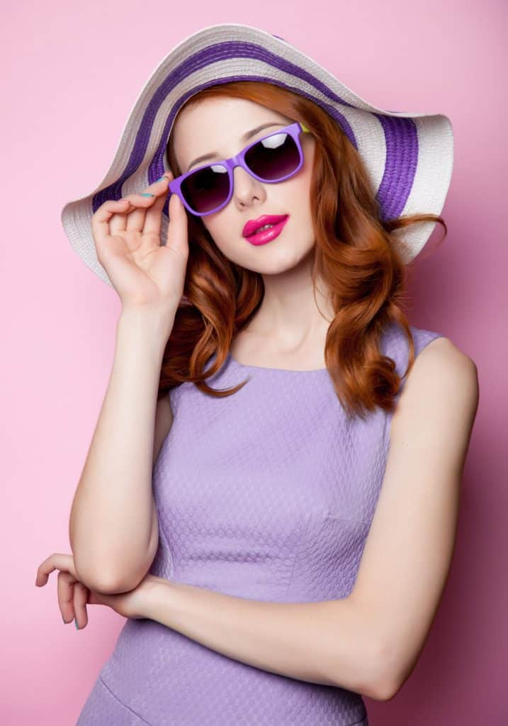 Young style redhead girl in sunglasses and purple clothes on pink background