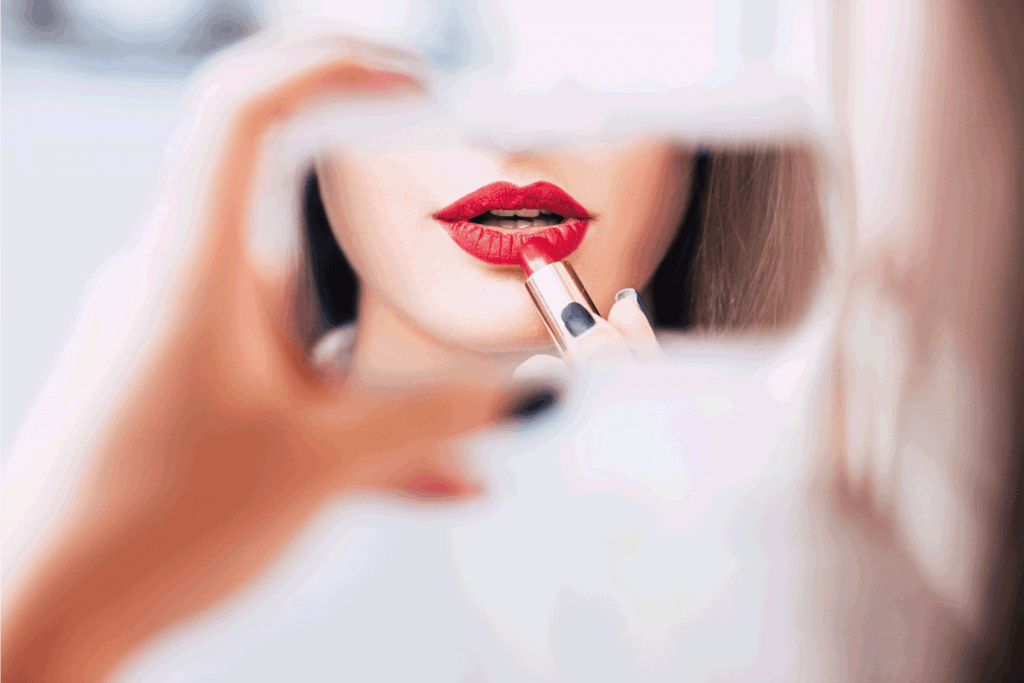 reflection of a woman using mirror wo apply red lipstick. What Color Blush Goes With Red Lipstick