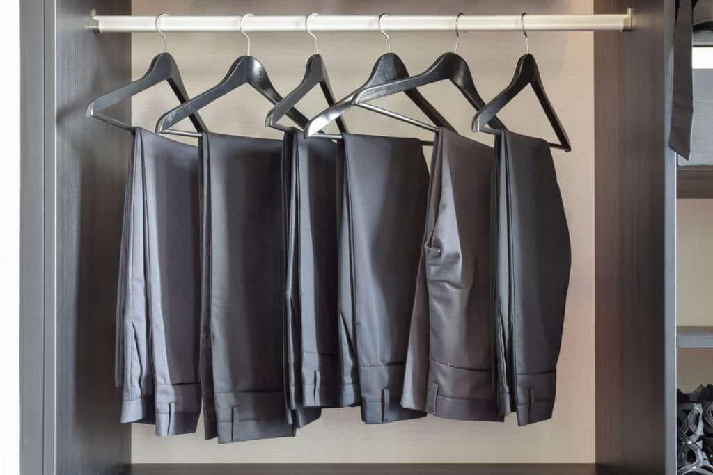 row of black pants hangs in wardrobe at home