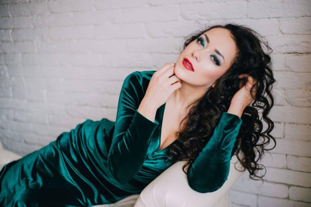 A beautiful fairly shaped woman wearing a green dress and wearing a red lipstick
