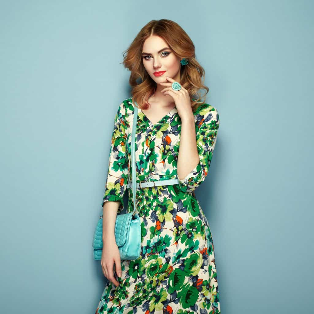 A beautiful gorgeous woman a floral green dress, clutch bag, and red lipstick