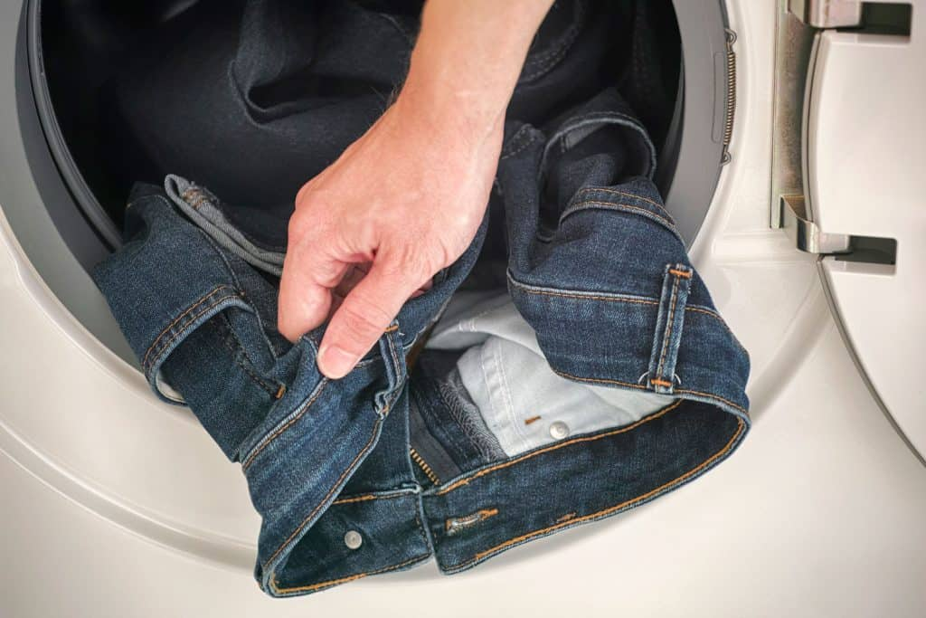 A man putting his jeans inside the washing machine
