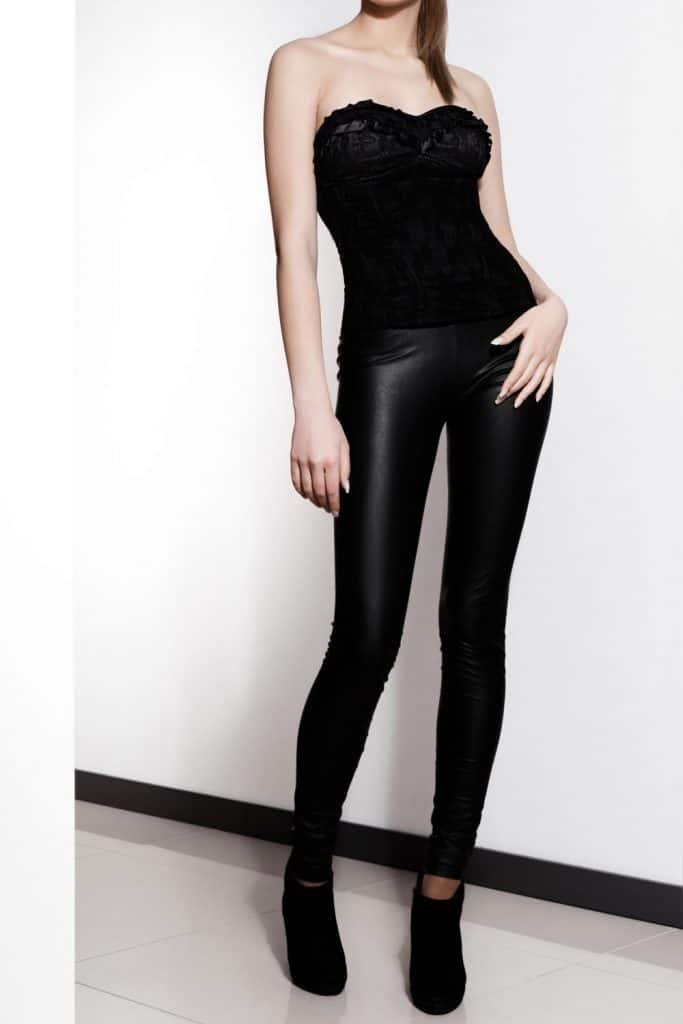 A tall model wearing black leather pants and black high heeled sandals