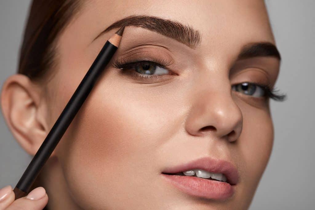 A woman applying eyeshadow on her eyebrow