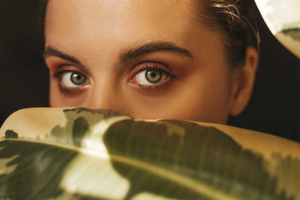 A woman looking at the camera with intent with her green eyes and dark brown eyeshadow, What Color Eyeshadow For Green Eyes?