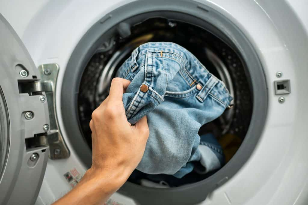A woman putting her jeans inside the washing machine, Should You Wash Jeans Inside Out?