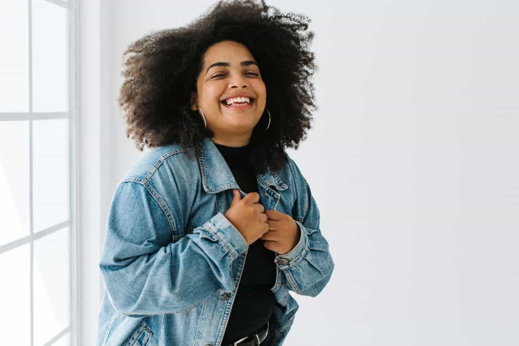 A woman with nice hair tucking in her denim jacket
