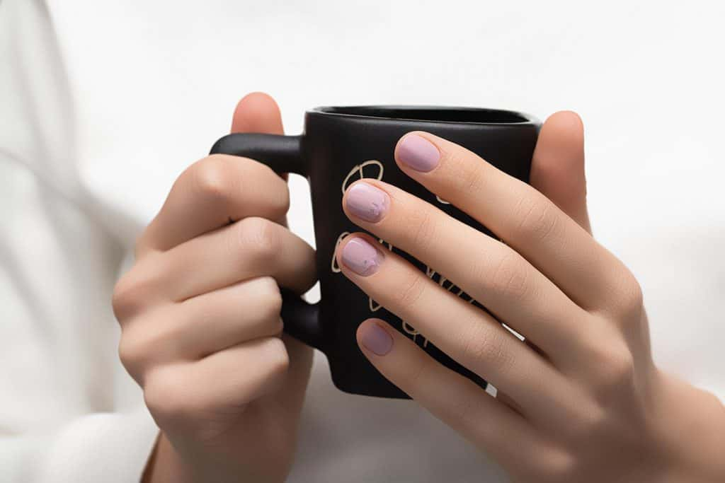 Beautiful female in white dress with perfect pink nails design holding coffee cup
