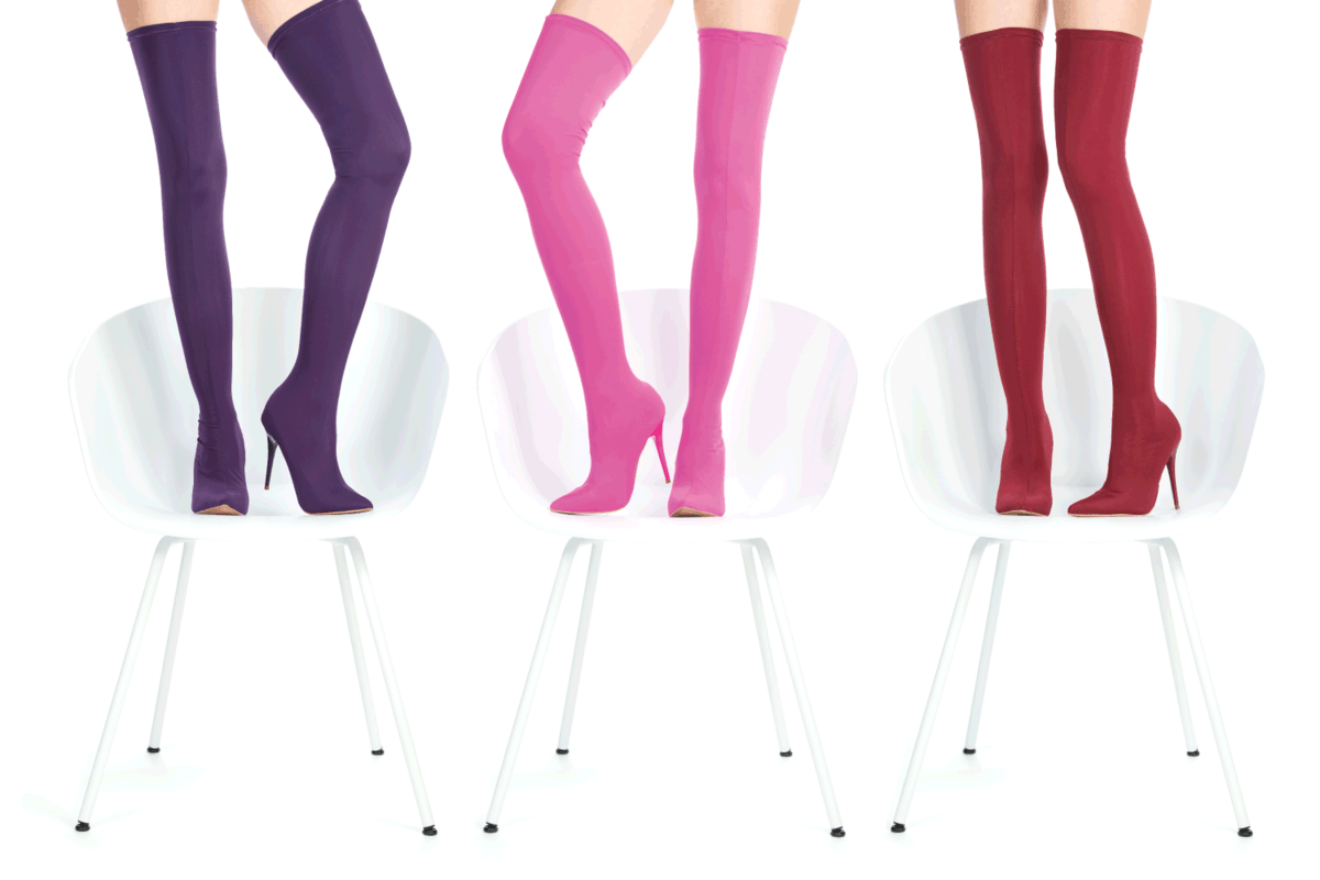 Beautiful female legs in glamorous and colorful thigh-high boots standing on white chairs against a white background