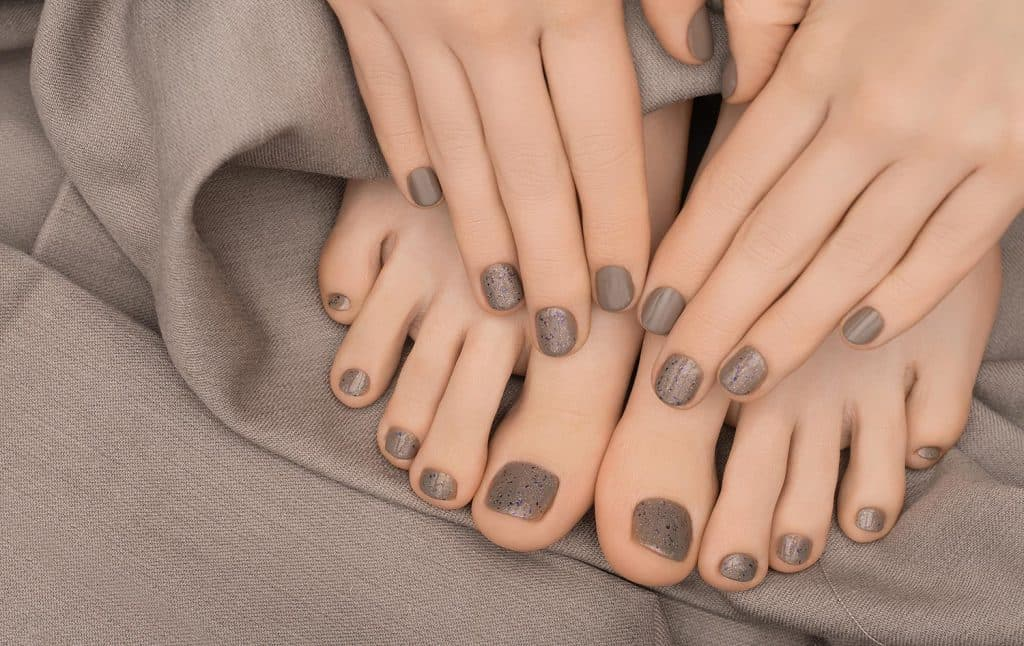 Beige nail polish manicure and pedicure on brown fabric