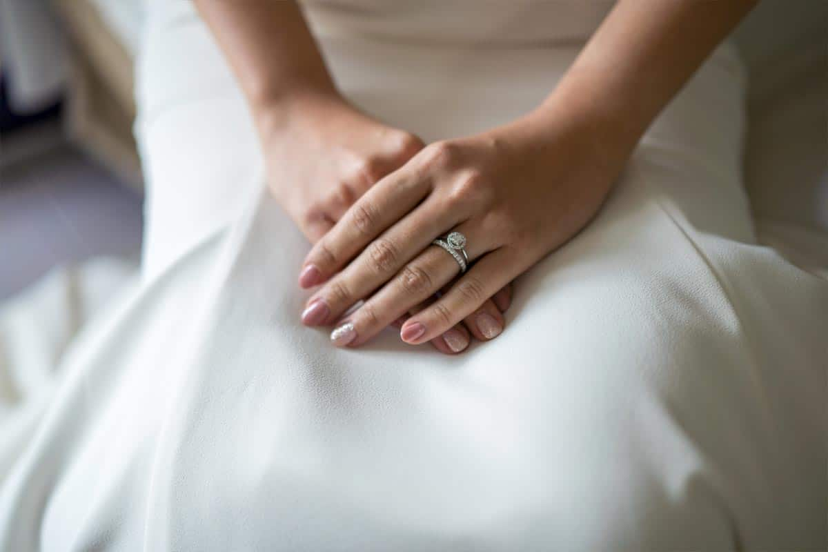 Woman with pink nails dressed in white wedding dress, What Nail Color Goes With A White Dress?