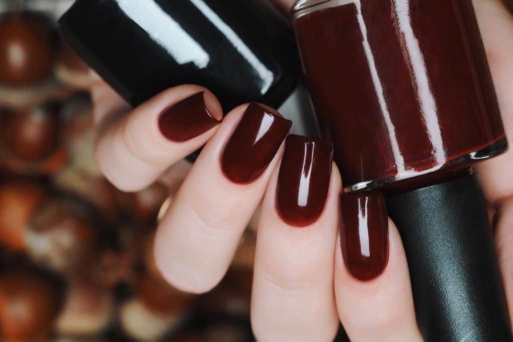Burgundy brown manicure on a background of acorns