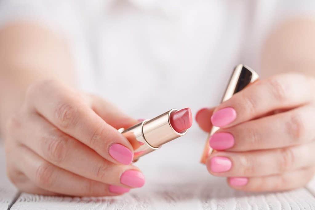 Hand holding pink lipstick