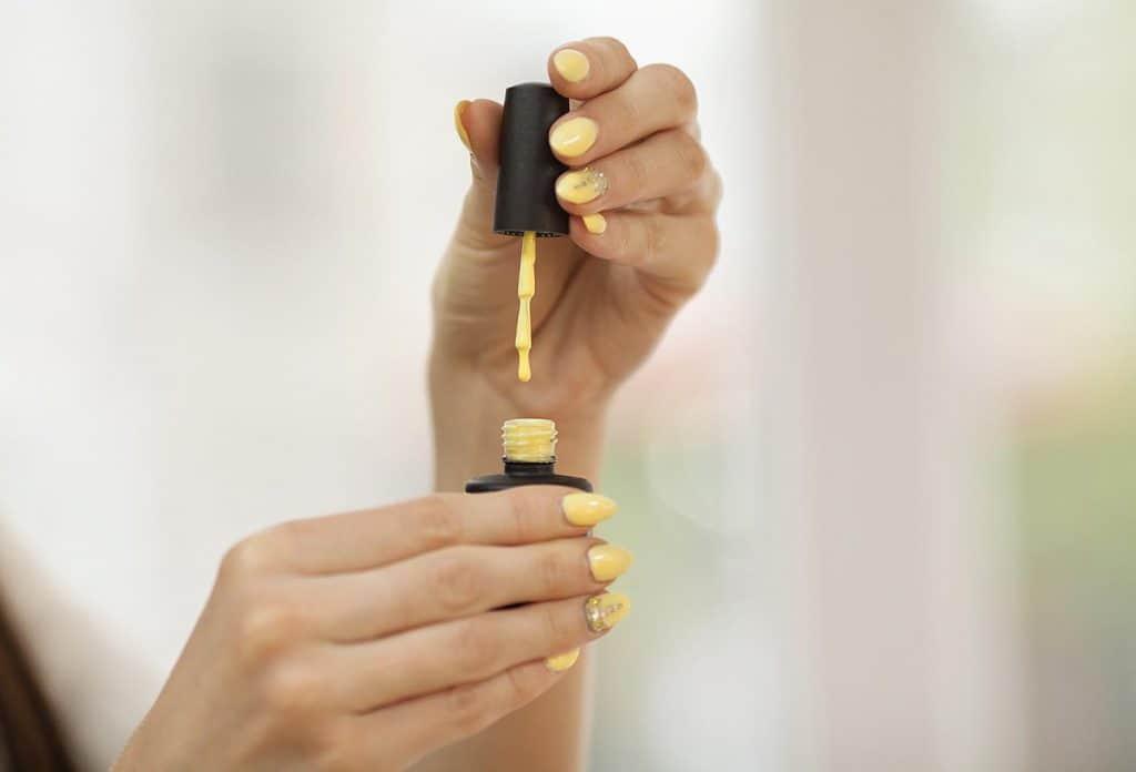 Hands holding yellow nail polish tube and cap with nail brush