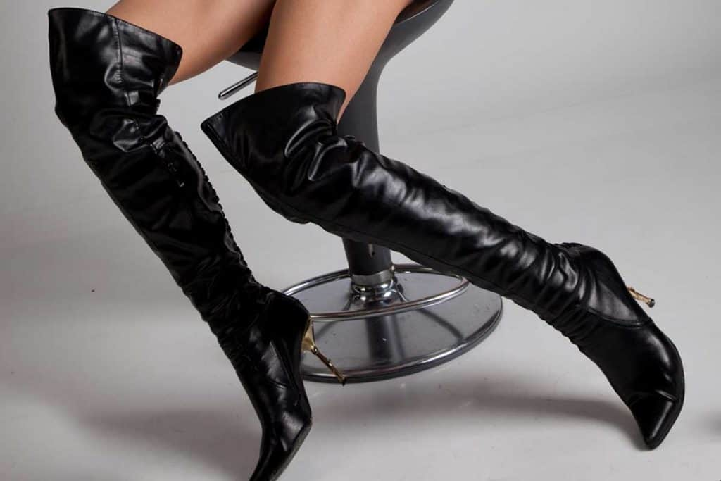 Model sitting on a stool wearing thigh high boots, How To Stretch Thigh High Boots - With A Few Methods To Try!