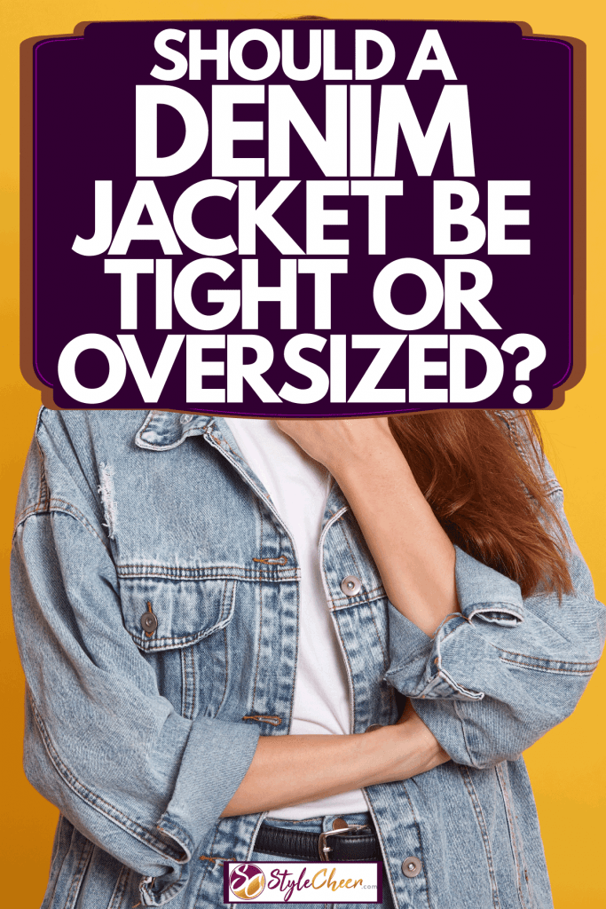 An attractive woman wearing an oversized denim jacket on a yellow background, Should A Denim Jacket Be Tight Or Oversized?