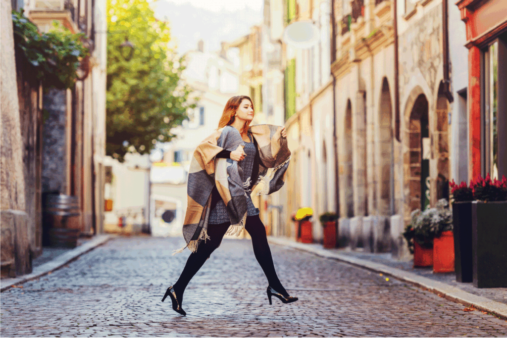 Young fashion 20 year old girl with red hair running down the street, wearing light dress, black tights, high heel shoes and warm plaid jacket. Do Thigh High Boots Make You Look Taller Or Shorter