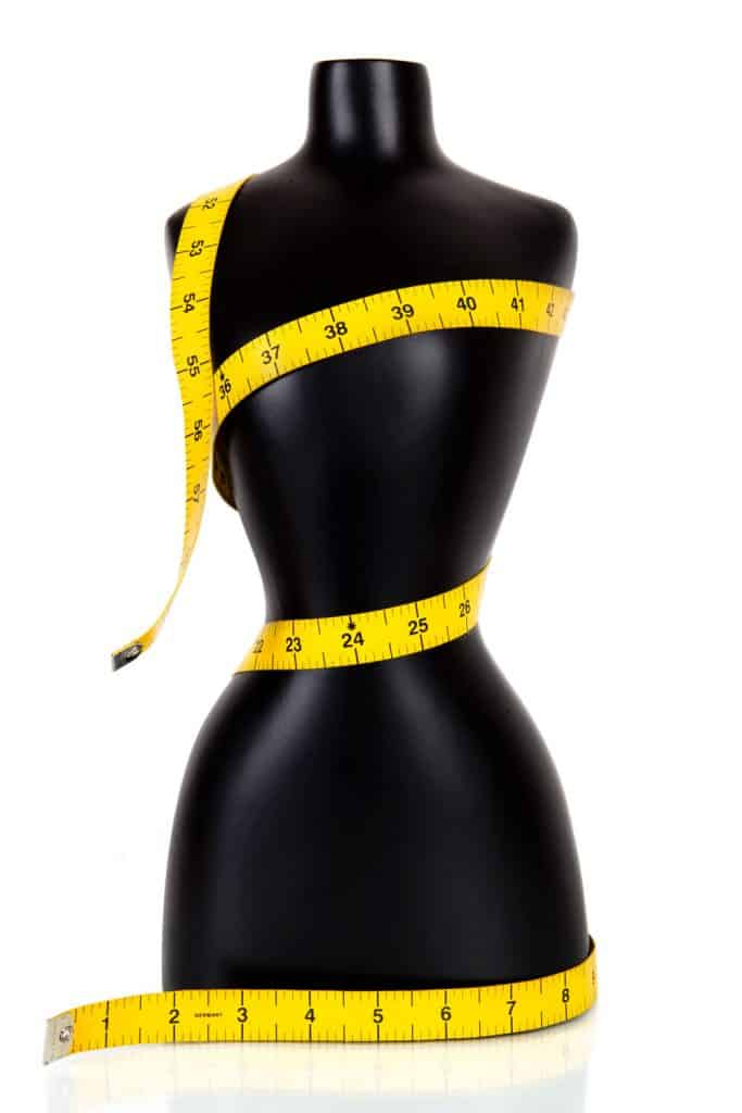 A yellow measuring tape wrapped around a black manikin