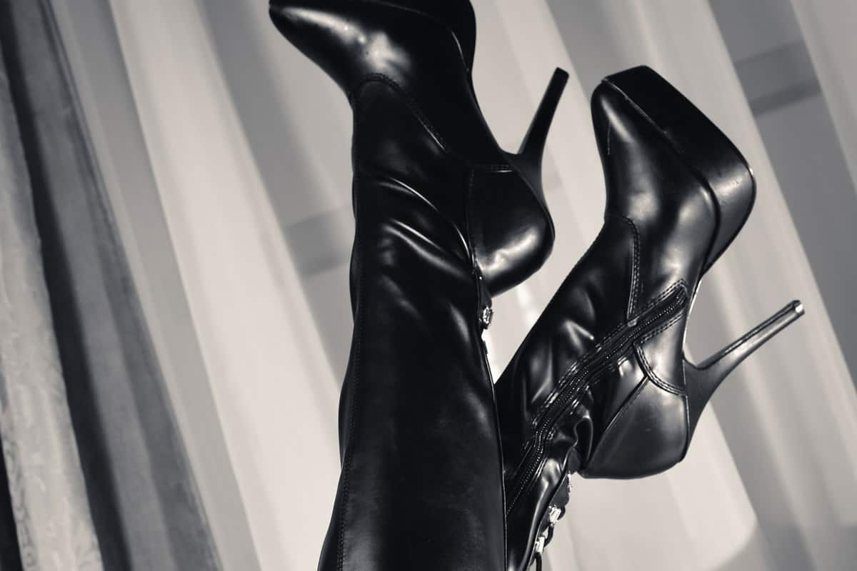 Thigh high boots worn by a woman lying on the couch, What Dress To Wear With Thigh High Boots? [6 Stunning Options Explored!]